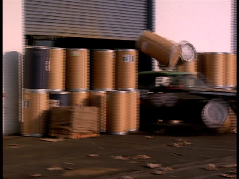 A tracking shot following a taxi cab as it races through a warehouse door and crashes into the harbor.