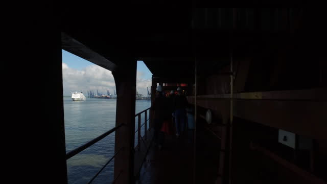 Tracking shot following crew members walking along a deck of a container ship.