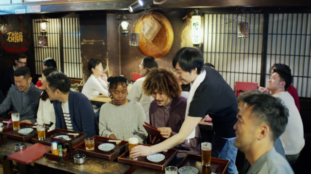 Tracking Shot Following Waiter Through Crowded Tokyo Restaurant