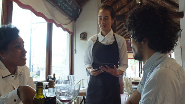 stockvideo's en b-roll-footage met tracking shot na serveerster nemen orde en walking away door argentijnse parrilla restaurant - mid volwassen koppel