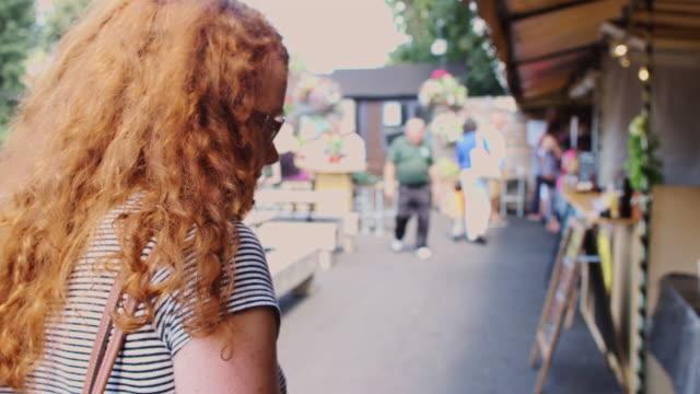 vidéos et rushes de tracking shot following young woman through market - marché