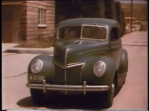 1939 tracking shot ford driving on suburban street - 1939 stock videos and b-roll footage