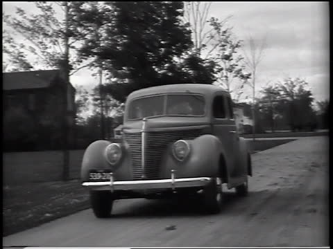 b/w 1937 tracking shot ford v-8 standard sedan driving on road past houses / commercial - ford motor company stock videos and b-roll footage