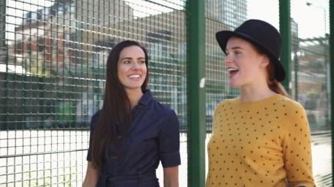 tracking shot - friends walking, talking, smiling - female friendship stock videos & royalty-free footage
