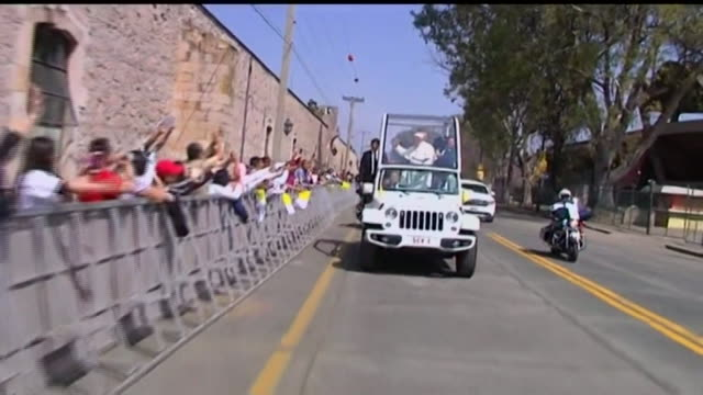 tracking shot from car, pope francis rides popemobile through street in morelia, mexico as bystanders cheer - morelia video stock e b–roll