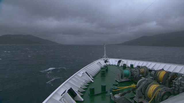 vídeos de stock e filmes b-roll de pov tracking shot from the prow of a ship as it travels along the stormy northern coastline of norway.  - navio de passageiros