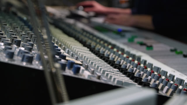 tracking shot from the side of a sound mixing console as it is being used - mixing stock videos & royalty-free footage