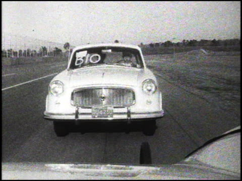 vídeos de stock, filmes e b-roll de tracking shot front end of 1960 amc rambler american custom as it drives on daytona speedway track; is from rear window of lead vehicle / rambler on... - tremido