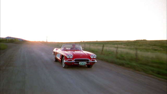 tracking shot front view man and young boy driving in 1960s corvette convertible on rural road - chevrolet stock videos & royalty-free footage