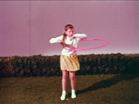 1959 tracking shot girl standing on studio lawn using plastic hoop with various parts of her body / educational - 1950 1959 stock-videos und b-roll-filmmaterial