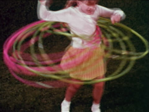 vídeos de stock e filmes b-roll de 1959 tracking shot girl standing on studio lawn with 6 plastic hoops / educational - 1950 1959