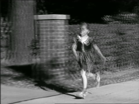 b/w 1948/49 tracking shot girl with braids skipping + running on suburban sidewalk - plaits stock videos and b-roll footage