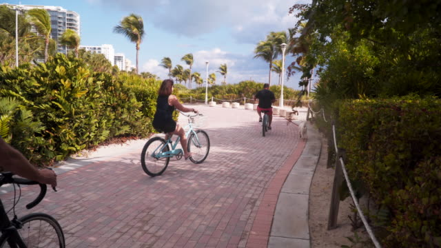 tracking shot, group of cyclists on miami beach pathway - フロリダ州点の映像素材/bロール