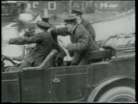 b/w 1915 tracking shot group of keystone kops in car driving crazily on road + pointing at something offscreen - 1910 stock videos & royalty-free footage