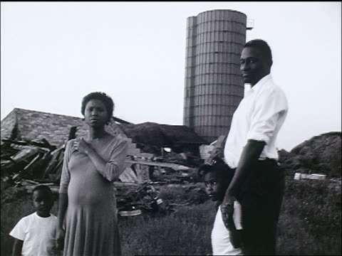vidéos et rushes de b/w tracking shot homeless black family standing in dump / zoom in - african american ethnicity