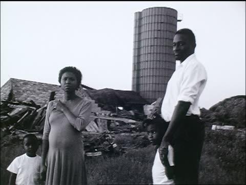 vidéos et rushes de b/w tracking shot homeless black family standing in dump / zoom in - afro américain