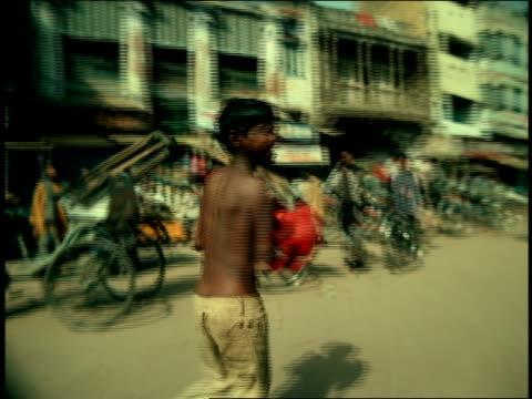 tracking shot Indian boy wearing boxing gloves running through crowded street / Varanasi, India