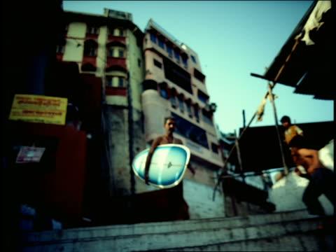 vídeos de stock e filmes b-roll de tracking shot indian man carrying surfboard down steps (ghats) / people passing on steps / varanasi, india - super exposto