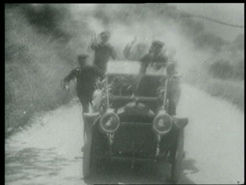 b/w 1915 tracking shot keystone kops driving car + firing guns toward camera / short - 1915年点の映像素材/bロール