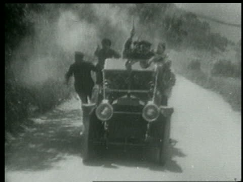 B/W 1915 tracking shot Keystone Kops driving car + firing guns toward camera / short