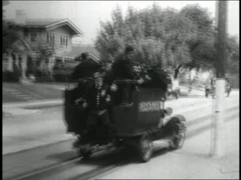 b/w 1935 rear view tracking shot keystone kops on police truck driving recklessly across trolley tracks - 1935 stock-videos und b-roll-filmmaterial