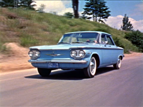 vídeos de stock e filmes b-roll de 1960 tracking shot light blue corvair driving on country road / industrial - general motors