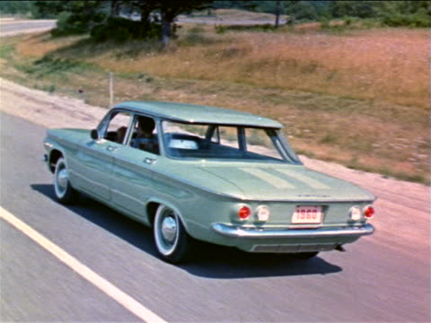 1960 rear view tracking shot light blue corvair driving on country road / industrial - 1960 stock-videos und b-roll-filmmaterial
