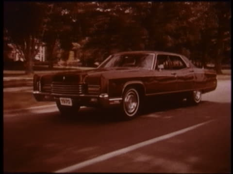 1970 tracking shot lincoln continental driving on suburban street - ford motor company stock videos and b-roll footage