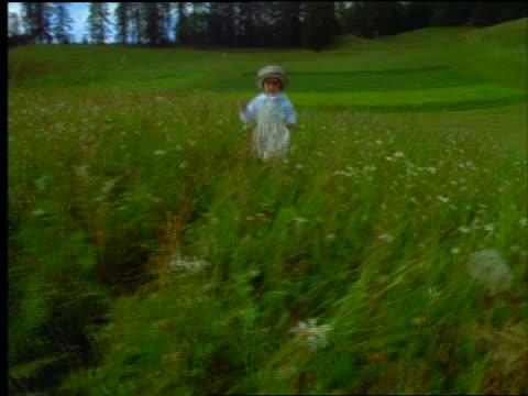 tracking shot little girl in hat walking through green meadow - endast flickor bildbanksvideor och videomaterial från bakom kulisserna