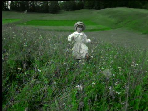 grey tracking shot little girl in hat walking through green meadow - endast flickor bildbanksvideor och videomaterial från bakom kulisserna