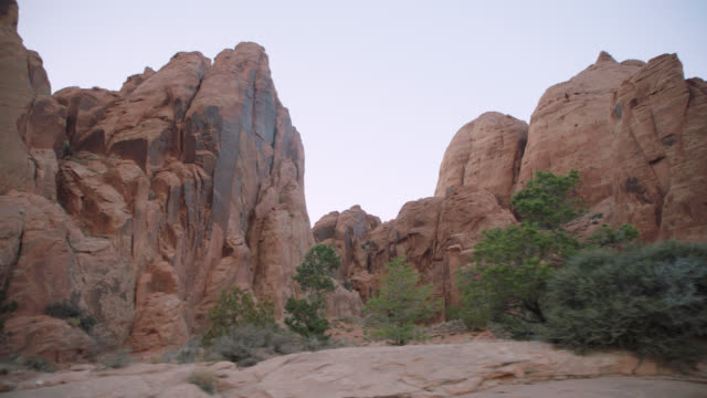 tracking shot looking up at rugged sandstone rock formations near moab, utah. - red rocks stock videos and b-roll footage