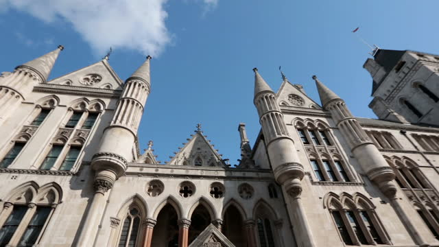 tracking shot looking up at the gothic revival architecture of the royal courts of justice in london. - royal courts of justice stock videos & royalty-free footage
