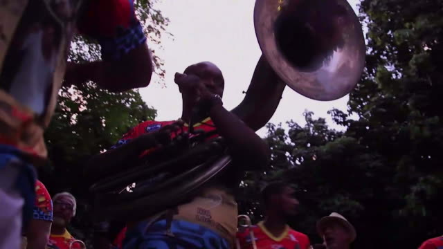 tracking shot, low angle member of band wears red shirt and plays oboe in the middle of the street during banda de ipanema festival in rio de... - ブラスバンド点の映像素材/bロール
