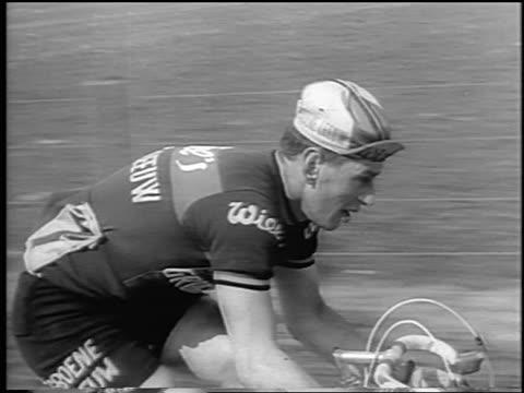 b/w 1964 tracking shot male cyclist racing in tour de france / newsreel - ツール・ド・フランス点の映像素材/bロール