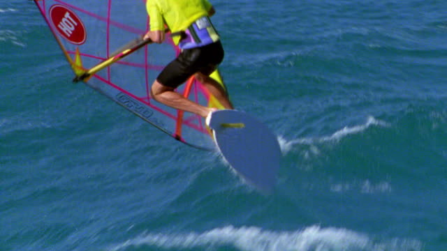 AERIAL tracking shot male windsurfer jumping over wave + landing roughly in water / Hawaii