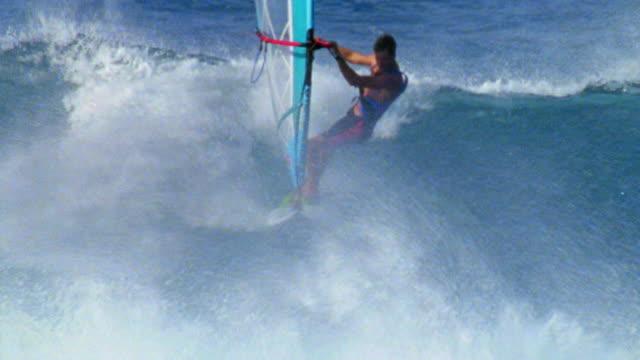 aerial tracking shot male windsurfer riding waves on ocean / hawaii - windsurf video stock e b–roll