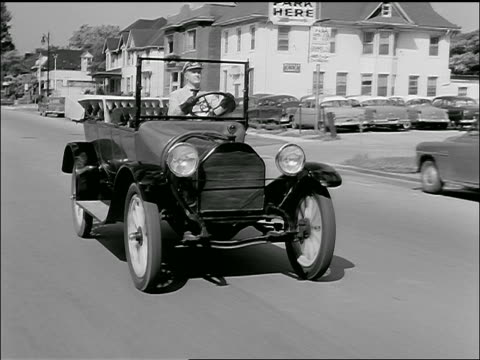b/w 1957 tracking shot man driving 1910's antique car, possibly a chevrolet, on suburban street, turns corner - model t stock videos and b-roll footage