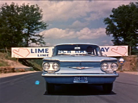 1960 tracking shot man driving light blue corvair under lime rock raceway sign on track / industrial - general motors stock videos & royalty-free footage