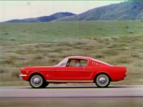 vídeos de stock, filmes e b-roll de 1965 side tracking shot man driving red ford mustang on country road / hills in background / industrial - 1965