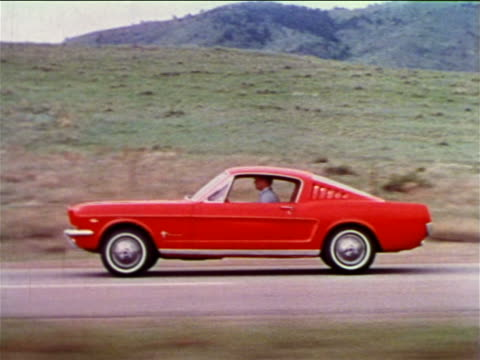 1965 SIDE tracking shot man driving red Ford Mustang on country road / hills in background / industrial