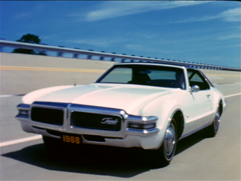 1968 tracking shot man driving white oldsmobile toronado on test track / industrial - general motors stock videos & royalty-free footage