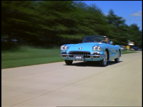 1957 tracking shot man in baby blue 1957 chevrolet corvette convertible driving on road - chevrolet stock videos & royalty-free footage