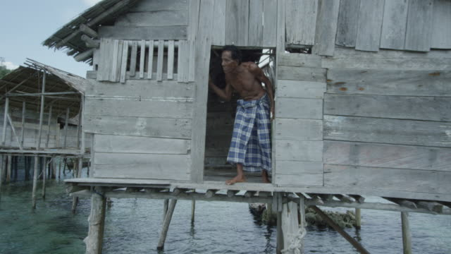 vídeos de stock e filmes b-roll de tracking shot, man in fishing hut in indonesia - indonesia
