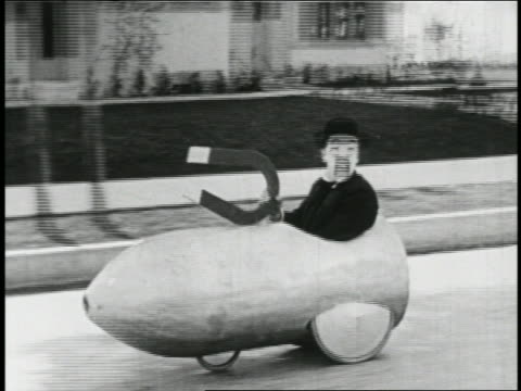 b/w 1923 tracking shot man (snub pollard) in mini-car with giant magnet moving along street / feature - 1923年点の映像素材/bロール