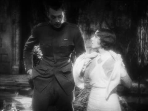 b/w 1932 tracking shot man in ww i uniform nurse walking in garden / feature - 1932 stock videos & royalty-free footage