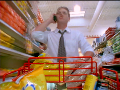 vidéos et rushes de fast tracking shot man pushing shopping cart thru aisle of grocery store + talking on cellular phone - historique