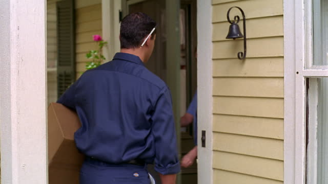 tracking shot ms man walking on path with package, ringing doorbell, + woman signing for delivery - pacco video stock e b–roll