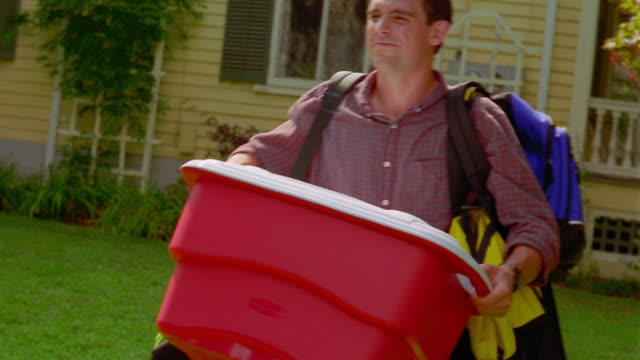 vidéos et rushes de ms tracking shot man walking with luggage + cooler across yard / house in background - carrying