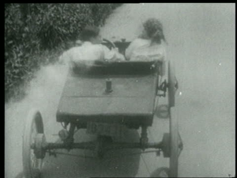 b/w 1915 rear view tracking shot man + woman driving sports car on road ducking bullets from unseen source - 1915年点の映像素材/bロール