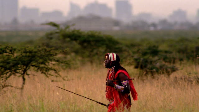 ms tracking shot masai tribesman walking across plain with nairobi in background / kenya - viewpoint stock videos & royalty-free footage